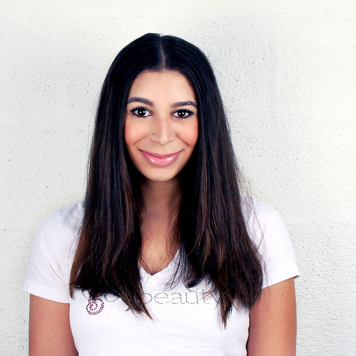 smiling brunette, wearing Got Beauty shirt in front of white backdrop